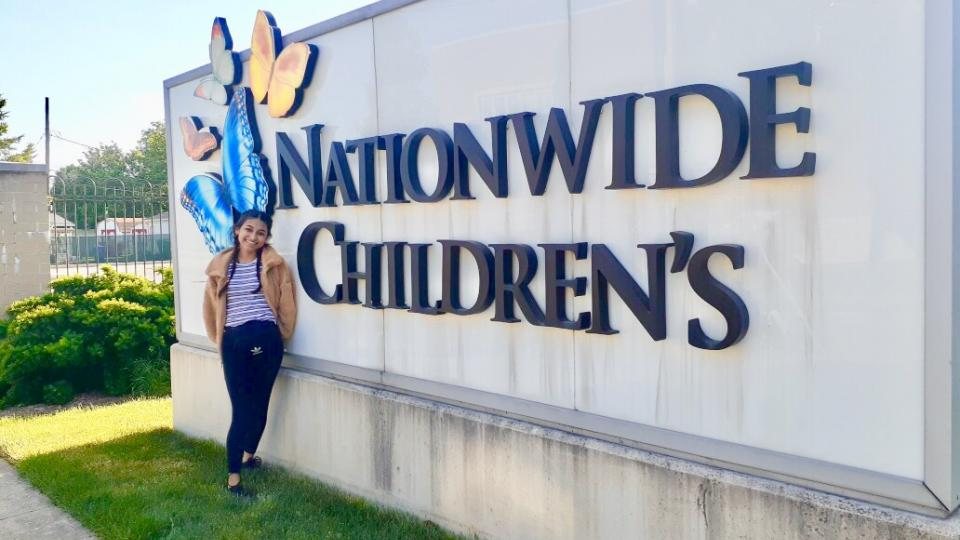 Evelyn Navarro stands in front of the sign at the cancer center where she was a pediatric cancer research intern.