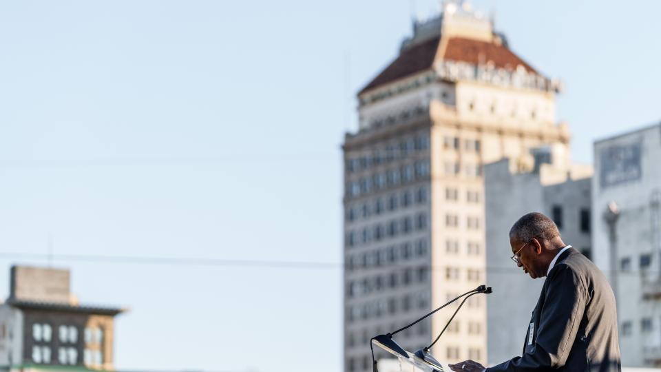 Joseph Jones, Ph.D., FPU President, prays with the Guarantee Bank Building in the background