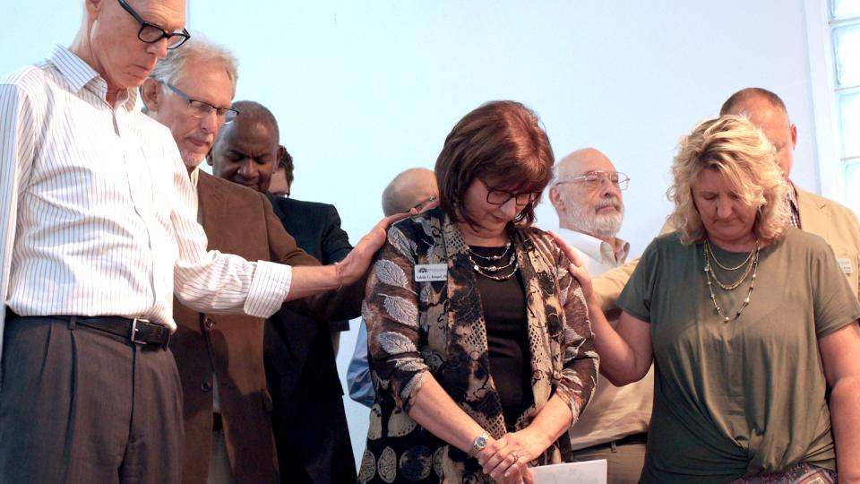 Faculty and others from Fresno Pacific Biblical Seminary pray with Valerie Rempel, Ph.D., at an installation convocation.