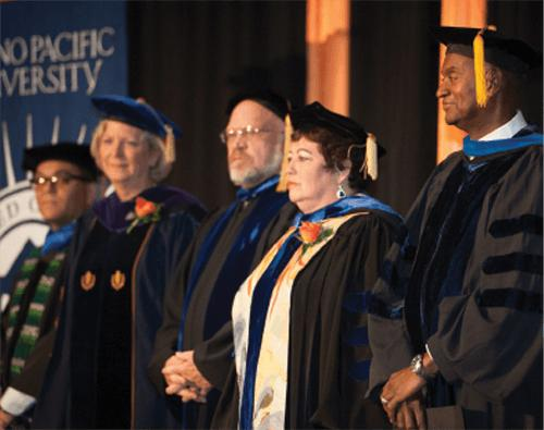 Faculty in regalia join Dr. Jones on stage