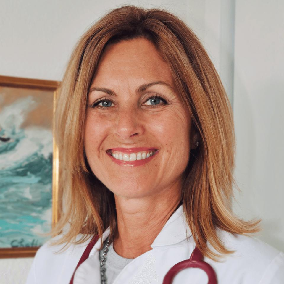Christine Burg portrait in office wearing scrubs and stethoscope