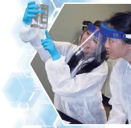 Two students wearing face shields and examining flask