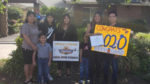 An FPU social work graduates celebrates with family and signs on their front lawn