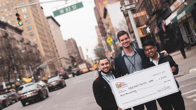 "FPU business students (from left) Freddie Lopez, Austin Hussain and Miguel Bermudez  take ""big check"" of their GoLiveServe winnings to the streets of New York City."