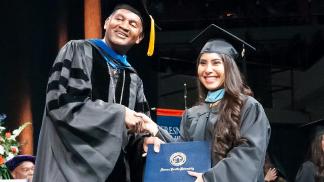 Fresno Pacific University President Joseph Jones, Ph.D., stands with a new graduate in 2018