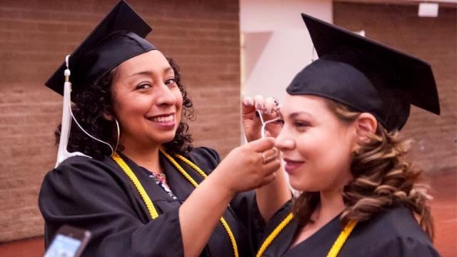 Grad helping another grad hang tassel on hat before commencement