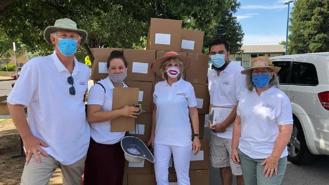 CCT staff masked and handing out food. From left are Randy White, D.Min., CCT executive director; Laura Flores, certificado coordinator; Cathleen Lawler, community relations officer; Carlos Huerta, associate director; and Jeanette Jaurena, administrative program coordinator.