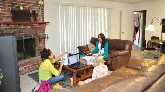 Three smiling students gather in renovated FPU student house to study