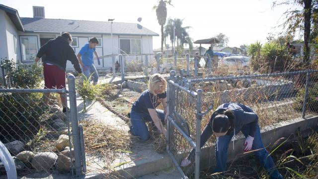 Members of the Mentoring/Connecting class cleaning the yard for a woman and her adult daughter