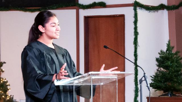 New graduate Viviana Vasquez speaks in the Butler Church sanctuary during FPU's Muticultural Baccalaureate