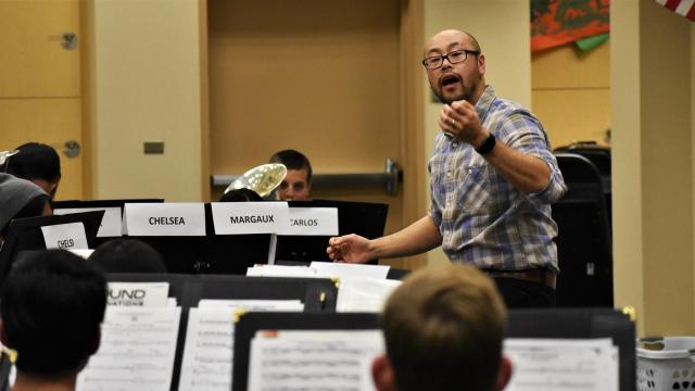 FPU music faculty Erik Leung gestures as he conducts students at the Clovis North High School Band Camp