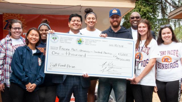 Students celebrate a gift to FPU's Sunbird Pantry with Fresno City Councilmember Luiz Chavez and Angulus Wilson, university pastor