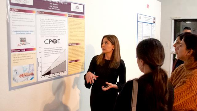 A student shares her poster presentation at FPU's Seventh Bi-Annual Graduate Research Symposium