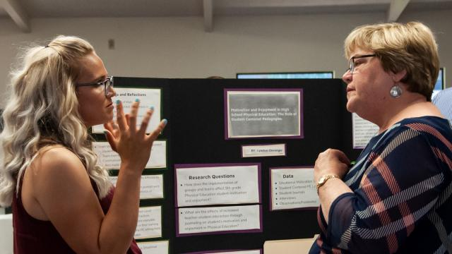 Lyndsie Clevenger, left, discusses her graduate research project with Linda Hoff, Ph.D., head of the FPU Teacher Education Divison