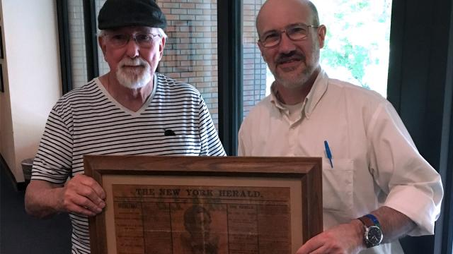 David Allen and Marshal Johnston, Ph.D., hold Allen's gift of an original framed newspaper page describing Lincoln's assassination
