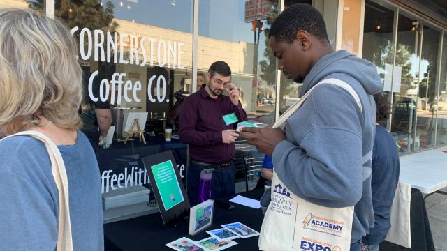 Visitors to the Social Enterprise EXPO check literature outside Cornerstone Coffee Company