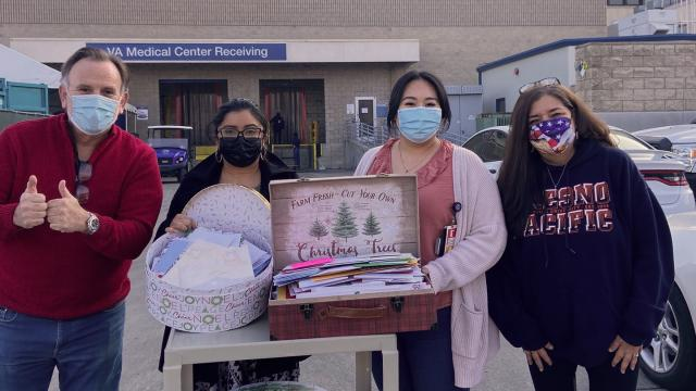 Four people and decorated boxes of Christmas cards: Left to right—David Black, Jenniffer Jeannette and Vivianne Xiong (both employees of VA Central California Healthcare System Voluntary Service) and Denise Baronian.