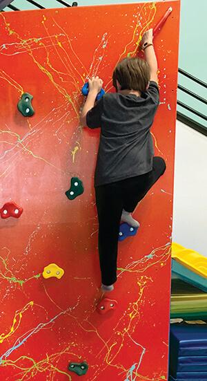 Child climbing on rock wall