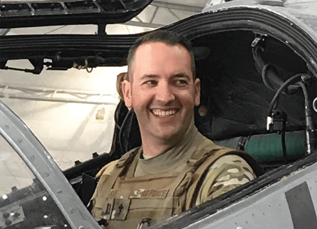 Rob Rose in Air Force uniform photographed smiling in cockpit